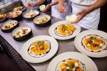 Media sección del chef comida en platos de guarnición - foto de stock