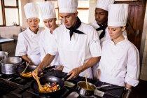 Jefe de cocina enseñando su equipo para preparar una comida en la cocina - foto de stock