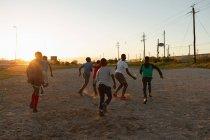 Niños jugando al fútbol en el suelo al atardecer - foto de stock