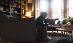Femme utilisant un ordinateur portable dans le salon à la maison — Photo de stock