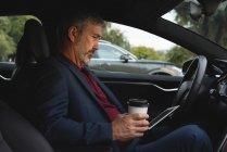 Vue latérale de l'homme d'affaires à l'aide de tablette numérique dans une voiture — Photo de stock