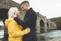 Glückliches junges Paar umarmt sich am Fluss — Stockfoto