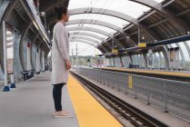 Thoughtful woman standing on platform at railway station — Stock Photo