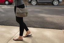 Partie basse de la femme marchant dans la rue — Photo de stock
