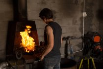 Herrero hembra calefacción herradura en el fuego en la fábrica - foto de stock