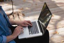 Sección media de la mujer usando el ordenador portátil en el parque - foto de stock