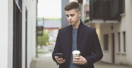 Giovane uomo che utilizza il telefono cellulare mentre prende il caffè — Foto stock