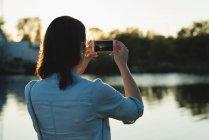 Vista posteriore della donna cliccando foto con il telefono cellulare — Foto stock