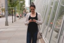 Beautiful woman using mobile phone in the city — Stock Photo