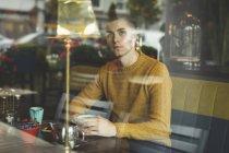 Homme regardant par la fenêtre tout en buvant le café en café — Photo de stock