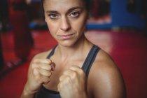 Уверенная женщина-боксер, занимающая боксерскую позицию в фитнес-студии — стоковое фото