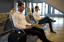 Businessmen reading newspaper in waiting area at airport terminal — Stock Photo