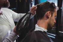 Asciugatura barbiere capelli cliente in negozio di barbiere — Foto stock