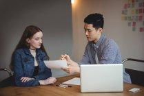 Dirigeants d'entreprises discuter au document dans office — Photo de stock