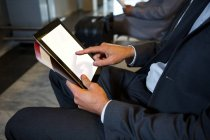 Mid-section of businessman using digital tablet while sitting at airport terminal — Stock Photo