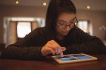 Femme utilisant une tablette numérique sur la table à la maison — Photo de stock