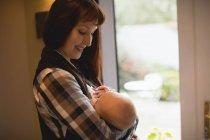 Mère joyeuse allaitant bébé à la maison fenêtre — Photo de stock