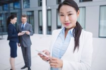 Portrait of a businesswoman using mobile phone in office — Stock Photo