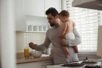 Отец завтракает, держа мальчика на кухне — стоковое фото