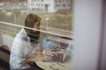 Femme d'affaires travaillant sur ordinateur portable dans le bureau derrière le verre — Photo de stock