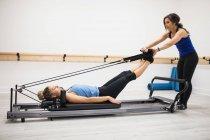 Trainerin unterstützt Frau bei Dehnübungen am Reformer im Fitnessstudio — Stockfoto