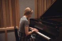 Жінка грає на фортепіано в музичну студію — стокове фото