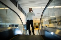Smiling man with suitcase talking on mobile phone on escalator in airport — Stock Photo