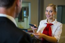 Female scanning the boarding pass with mobile phone at airport terminal — Stock Photo