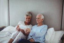 Старший пара, використовуючи цифровий планшетний ліжко в номері — стокове фото