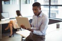 Бизнесмен, работающий за ноутбуком в офисе — стоковое фото