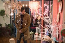 Man looking at chandeliers in vintage store — Stock Photo