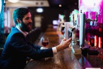 Businessman using mobile phone with glass of red wine at bar — Stock Photo