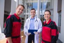 Retrato de médico sorridente e paramédico em pé no hospital — Fotografia de Stock