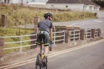 Вид сзади на велосипед атлета на сельской дороге — стоковое фото