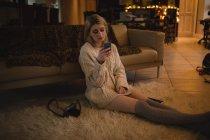 Женщина использует мобильный телефон, сидя дома — стоковое фото