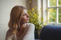 Belle femme regardant par la fenêtre dans le salon à la maison — Photo de stock