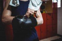 Boxer usando luvas de boxe no vestiário no estúdio de fitness — Fotografia de Stock