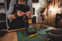 Mid-section of craftswoman working on a piece of leather in workshop — Stock Photo