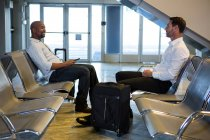 Passengers with suitcase interacting at waiting area in airport terminal — Stock Photo