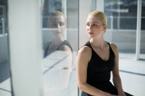 Ballerina sitting against glass window in the studio — Stock Photo
