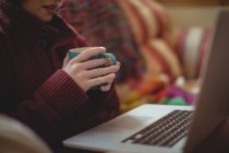 Mid-section of woman having coffee while using laptop on sofa — Stock Photo
