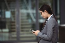 Businesswoman texting on mobile phone while standing at city street — Stock Photo