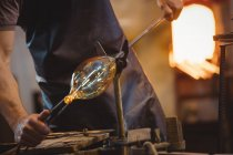 Mid section of glassblower shaping a molten glass at glassblowing factory — Stock Photo