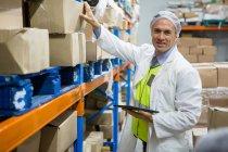 Técnico masculino manteniendo registro en tableta digital en fábrica de carne - foto de stock