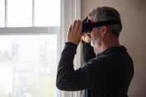 Uomo che utilizza cuffie realtà virtuale a casa — Foto stock