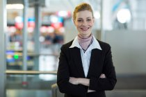 Portrait of smiling airline check-in attendant at counter in airport terminal — Stock Photo