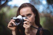 Красивая женщина, стоящая с камерой в лесу — стоковое фото