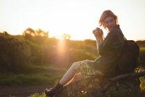 Donna premurosa seduta sulla roccia e con la fotocamera digitale in una giornata di sole — Foto stock