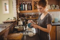 Woman preparing coffee in kitchen at home — Stock Photo