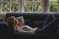 Задумчивая женщина лежит на диване в гостиной на дому — стоковое фото